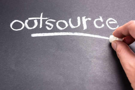 topic: Hand writing Outsource word topic on chalkboard
