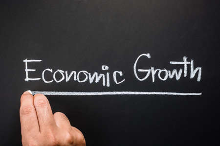 topic: Hand writing Economic Growth topic on chalkboard