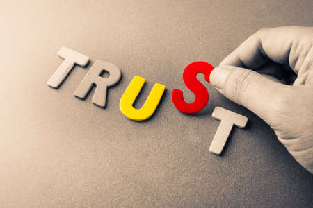 trust: Trust Us, hand arrange wood letters as Trust word with color letters of Us word inside