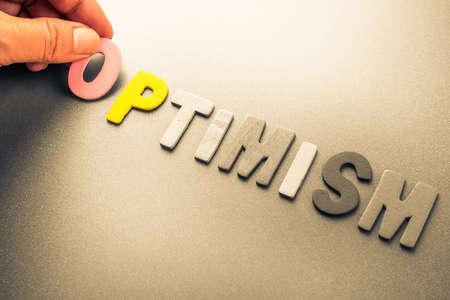 optimismo: Mano organizar letras de madera como palabra Optimismo Foto de archivo