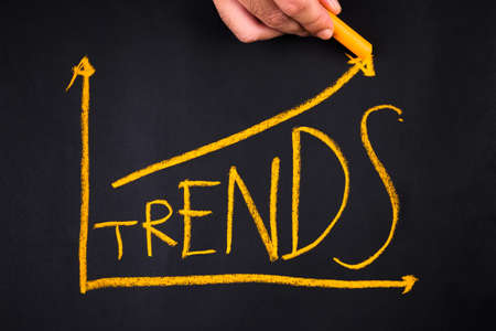 business trending: Hand writing Trends topic in growth graph on chalkboard Stock Photo