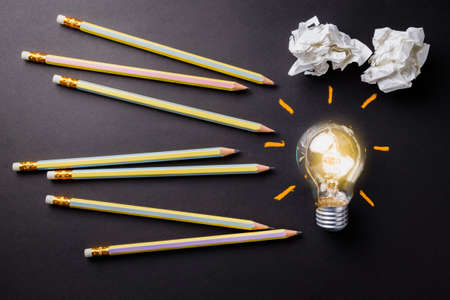 crease: Pencils and glowing light bulb, creative writing concept