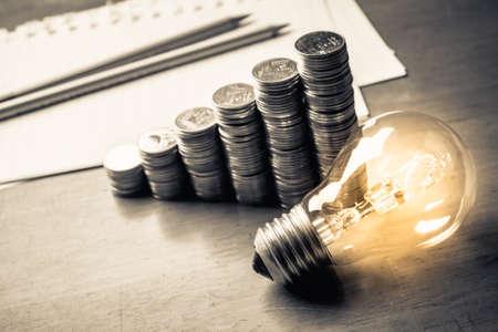 종이에 동전 계단 및 연필, 개념을 써서 돈을 만들기위한 아이디어와 빛나는 전구