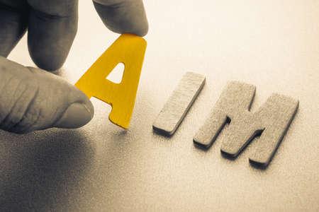 Hand arrange wood letters as Aim word