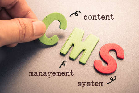 Hand arrange wood letters as CMS (Content Management System) Stock Photo