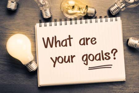 metas: ¿Cuáles son sus metas cuestionan como nota en el cuaderno con las bombillas