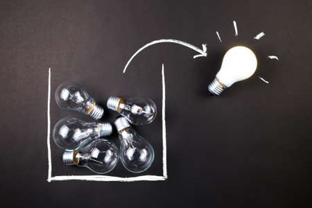 White light bulb glowing outside the drawing box, thinking outside the box or being different concept 写真素材