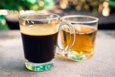 Black coffee and tea water on concrete table in the garden Archivio Fotografico