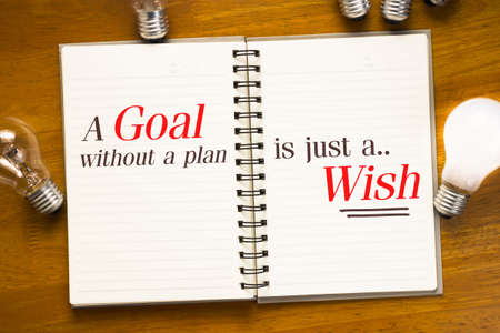 A Goal Without A Plan Is Just A Wish quotation in spiral notebook with light bulbs