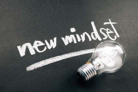 Handwriting of New Mindset topic with light bulb