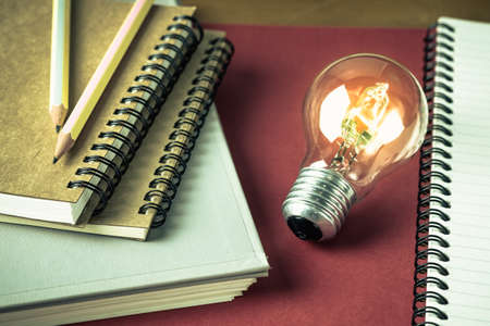 glowing light bulb: Glowing light bulb with many notebooks for creative writing concept Stock Photo