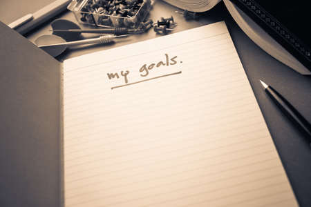 notebook page: Handwriting of My Goals on the first page of notebook with part of book, pen, thumbtack and dart on the table