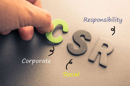 Closeup hand arrange wood letters as CSR abbreviation(Corporate social responsibility) Stockfoto