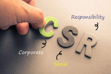 Closeup hand arrange wood letters as CSR abbreviation(Corporate social responsibility) Standard-Bild