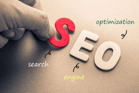 Mão organizar letras de madeira como SEO abreviatura (Search Engine Optimization)