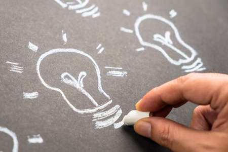 intent: Closeup hand drawing light bulb with chalk Stock Photo