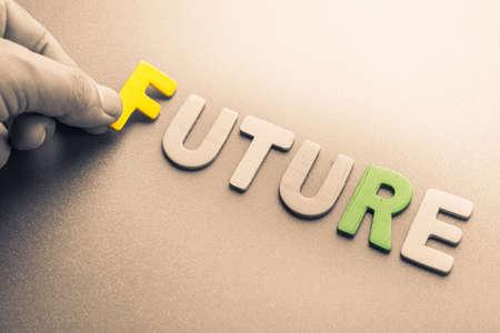 to arrange: Hand arrange wood letters as Future word