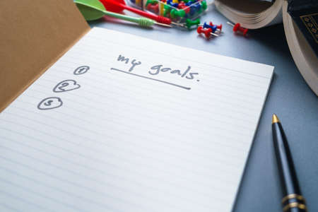 Handwriting of My Goals on the first page of notebook with part of book, pen, thumbtack and dart on the table