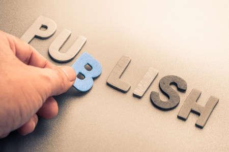 publicize: Hand arrange wood letters as Publish word