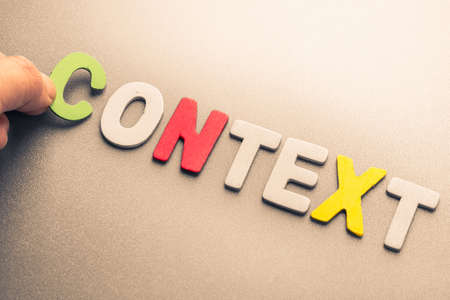 Hand arrange wood letters as Context word