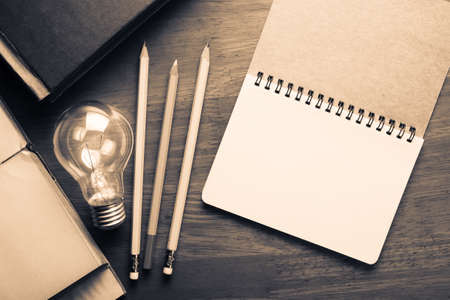 glowing light bulb: Opened spiral notebook with glowing light bulb on wood table