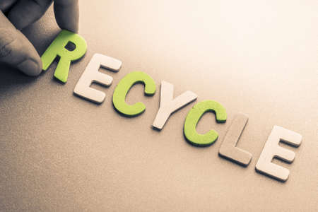 to arrange: Hand arrange wood letters as Recycle word Stock Photo