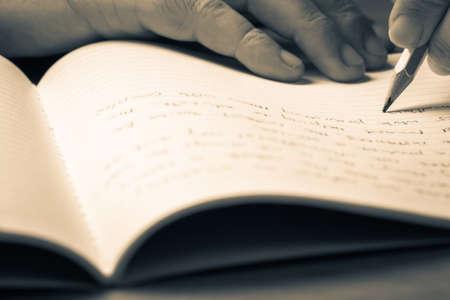 persona escribiendo: escritura de la mano Primer en el bloc de notas con lápiz