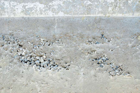 uncompleted: Abstract background of unfinished cement wall with embed stone Stock Photo