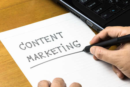 topic: Hand writing Content Marketing topic on paper with part of laptop Stock Photo