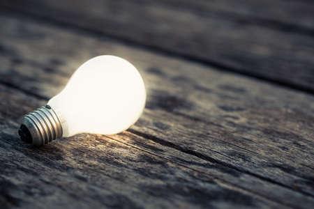 Bianco lampadina incandescente sul terreno di legno Archivio Fotografico - 48938501