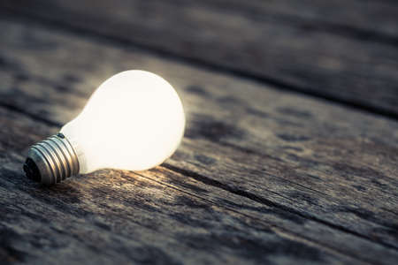 leuchtend: Weiß Glühbirne glühend auf dem Holz Boden