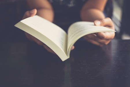 Vrouw zet haar armen op haar schoot en open boek te lezen