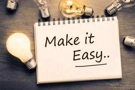 Make It Easy concept, handschrift op notebook met gloeilampen