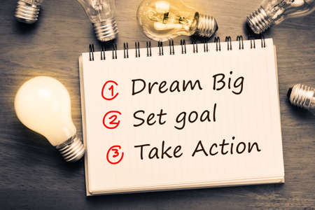 Dream Big - Set Goal - Take Action, handwriting on notebook with light bulbs Stockfoto