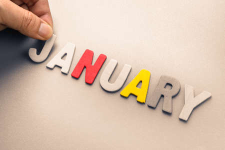 Hand arrange wood letters as January word