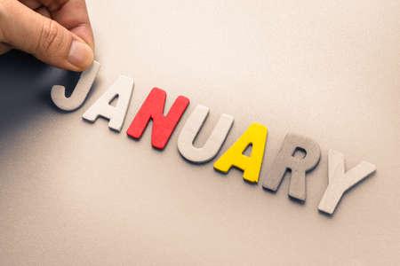 Mano ordenar letras de madera como Enero palabra Foto de archivo