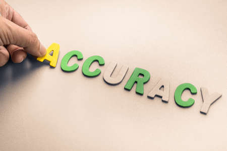 to arrange: Hand arrange wood letters as Accuracy word