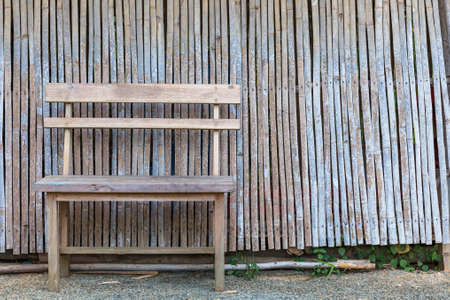 timber bench seat: Wood chair on irregular bamboo wall outside primitive Thai house