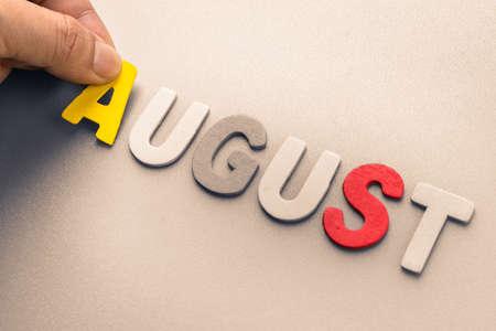 arrange: Hand arrange wood letters as August word Stock Photo