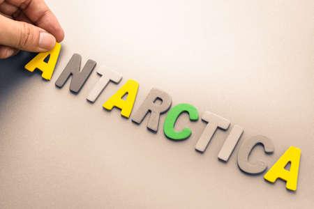 to arrange: Hand arrange wood letters as Antarctica word