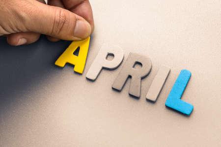 Hand arrange wood letters as April word