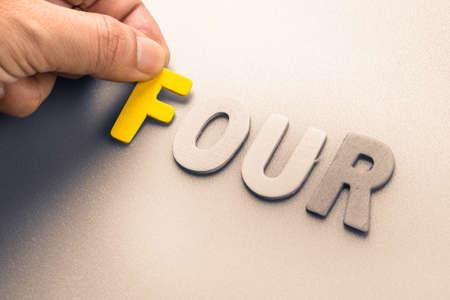 to arrange: Hand arrange wood letters as Four word