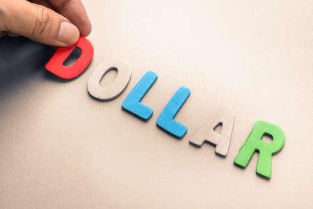 to arrange: Hand arrange wood letters as Dollar word