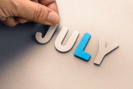 arrange: Hand arrange wood letters as July word Stock Photo