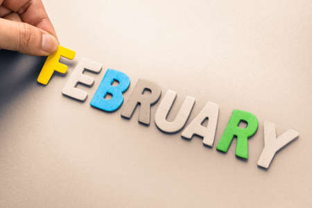 february: Hand arrange wood letters as February word