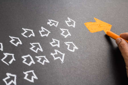 Gráfico de la mano de naranja flecha como líder de tendencia con muchas flechas blancas como seguidor