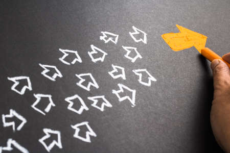 flecha direccion: Gráfico de la mano de naranja flecha como líder de tendencia con muchas flechas blancas como seguidor