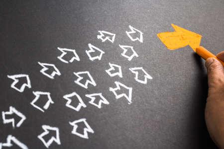 Main dessin flèche orange en tant que leader de la tendance avec de nombreuses flèches blanches comme suiveur