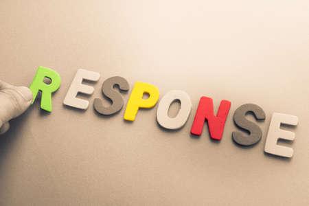 to arrange: Hand arrange wood letters as Response word Stock Photo