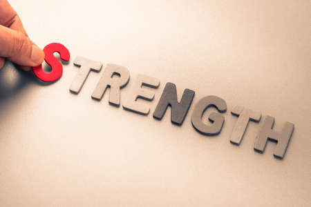 to arrange: Hand arrange wood letters as Strength word Stock Photo